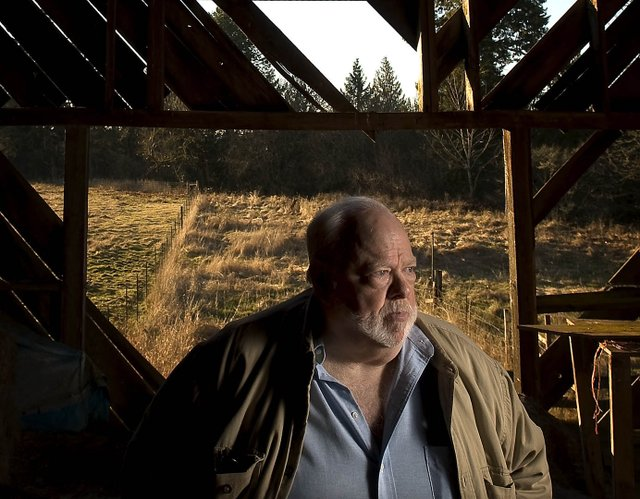 Chuck Cushman, executive director of the American Land Rights Association, stands inside an old barn on his Battle Ground property.He's fighting against Rialto Capital Management in hopes of spurring changes in how the government handles bank closures.